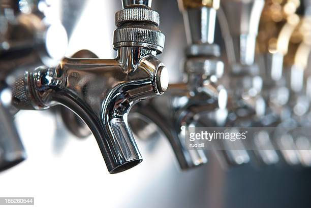 A line of silver beer taps in a row