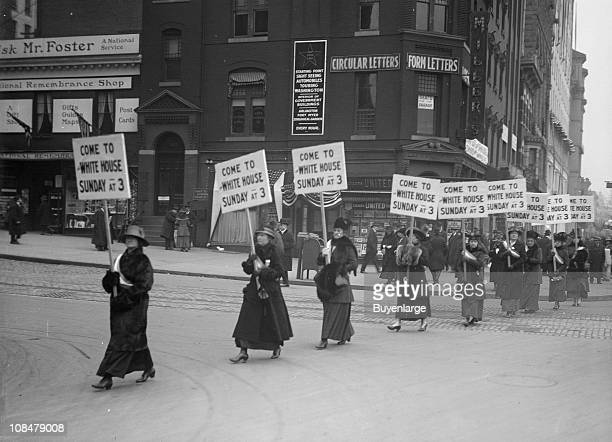 A line of suffragists march with banners that read 'Come to the White House Sunday at 3' Washington DC 1915