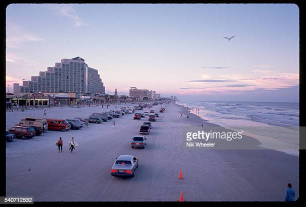 A line of traffic travels down Daytona beach near fun fairs and surfing activities in Florida