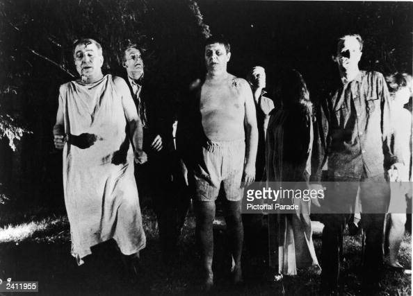 A line of undead 'zombies' walk through a field in the night in a still from the film 'Night Of The Living Dead' directed by George Romero 1968