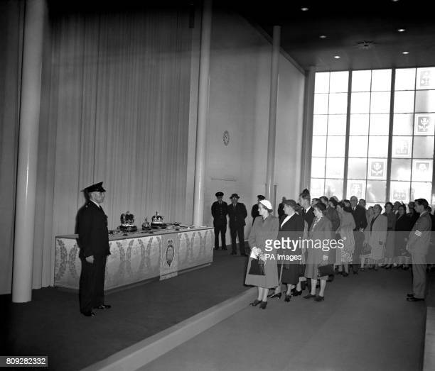 A line of visitors passing a display of replicas of the Regalia and Crown Jewels in the Westminster Abbey Annexe built specially for the Coronation...