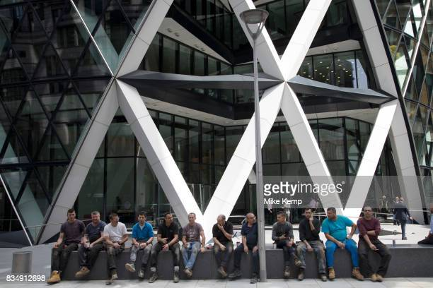 Line of workment taking a break sitting on a bench outside the Gherkin in the City of London England United Kingdom Exterior of the Gherkin at 1 St...