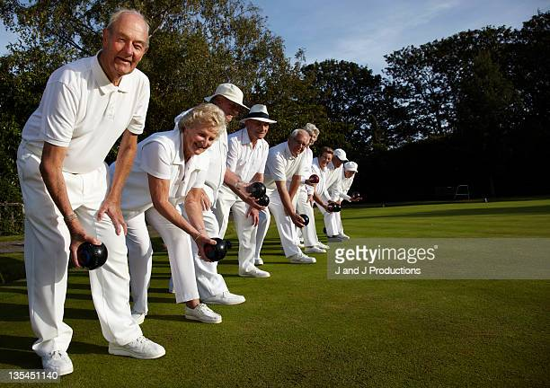 A line up of bowls players on a bowling green