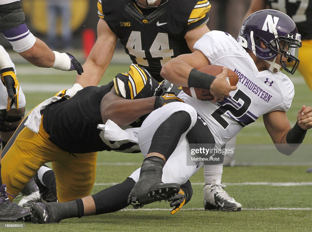 Linebacker Anthony Hitchens #31 of the Iowa Hawkeyes makes a sack on quarterback Kain Colter #2 of the Northwestern Wildcats during the second quarter on October 26, 2013 at Kinnick Stadium in Iowa City, Iowa. Iowa won 17-10.