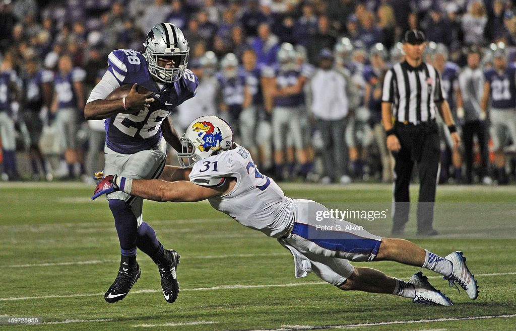 Linebacker <a gi-track='captionPersonalityLinkClicked' href=/galleries/search?phrase=Ben+Heeney&family=editorial&specificpeople=9689082 ng-click='$event.stopPropagation()'>Ben Heeney</a> #31 of the Kansas Jayhawks makes a diving tackle on running back Jarvis Leverett Jr. #28 of the Kansas State Wildcats during the second half on November 29, 2014 at Bill Snyder Family Stadium in Manhattan, Kansas. Kansas State defeated Kansas 51-13.