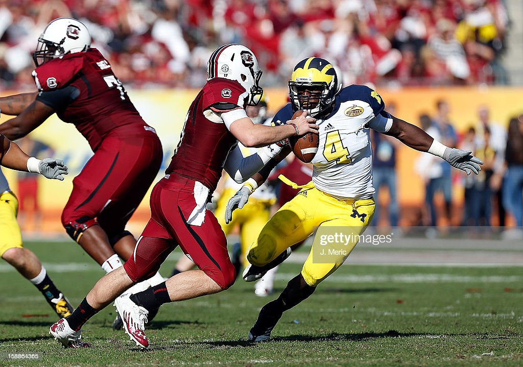 Linebacker Cam Gordon #4 of the Michigan Wolverines pressures quarterback Connor Shaw #14 of the South Carolina Gamecocks during the Outback Bowl Game at Raymond James Stadium on January 1, 2013 in Tampa, Florida.