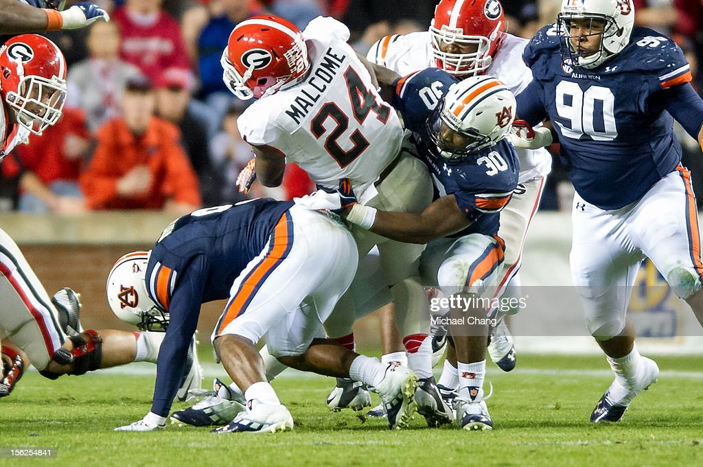 Linebacker Cassanova McKinzy #30 of the Auburn Tigers attempts to tackle tailback Ken Malcome #24 of the Georgia Bulldogs on November 10, 2012 at Jordan-Hare Stadium in Auburn, Alabama. Georgia defeated Auburn 38-0 and clinched the SEC East division.