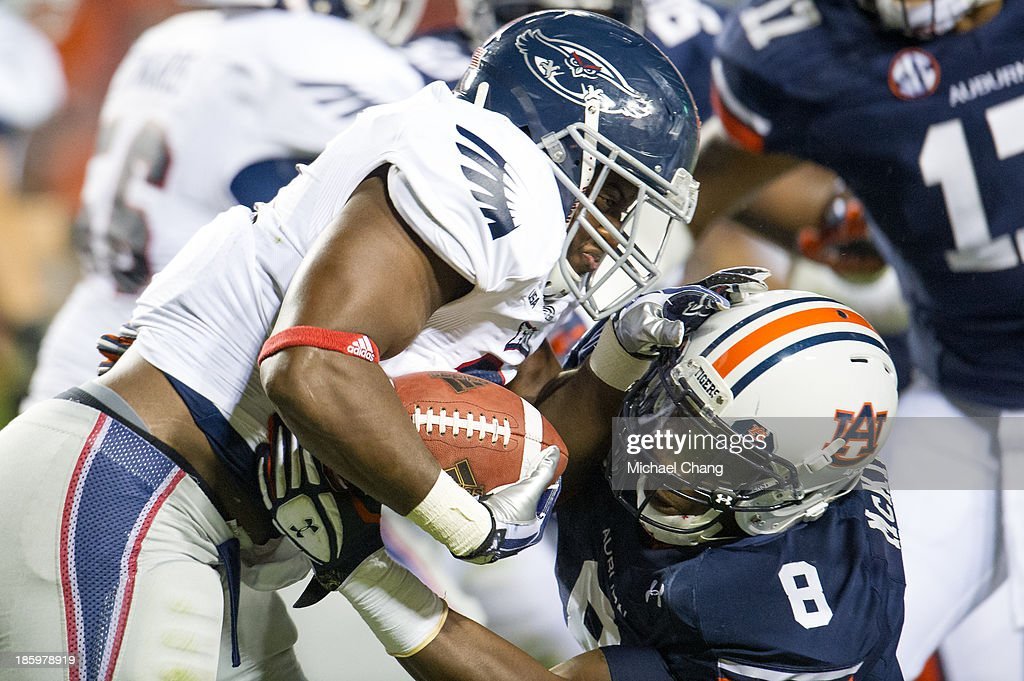 Linebacker Cassanova McKinzy #8 of the Auburn Tigers attempts to tackle running back Tony Moore #21 of the Florida Atlantic Owls during the second half of play on October 26, 2013 at Jordan-Hare Stadium in Auburn, Alabama. Auburn defeated Florida Atlantic 45-10.