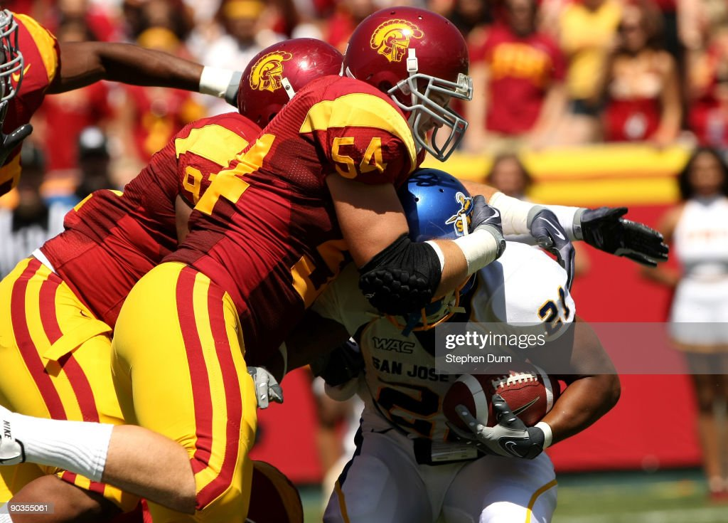 Linebacker Chris Gallipo and defensive tackle Jurrell Casey of the USC Trojans tie up running back Patrick Perry of the San Jose State Spartans on...