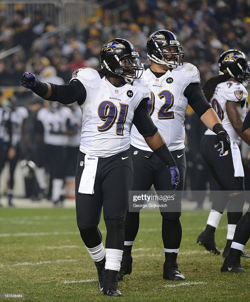 Linebacker Courtney Upshaw #91 of the Baltimore Ravens signals at the line of scrimmage as defensive lineman Haloti Ngata #92 looks on during a game against the Pittsburgh Steelers at Heinz Field on November 18, 2012 in Pittsburgh, Pennsylvania. The Ravens defeated the Steelers 13-10.
