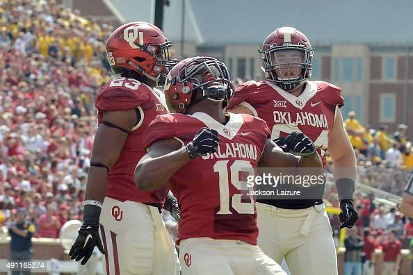 Linebacker Eric Striker of the Oklahoma Sooners celebrates a quarterback sack with teammates defensive tackle Matt Dimon and linebacker Devante Bond...