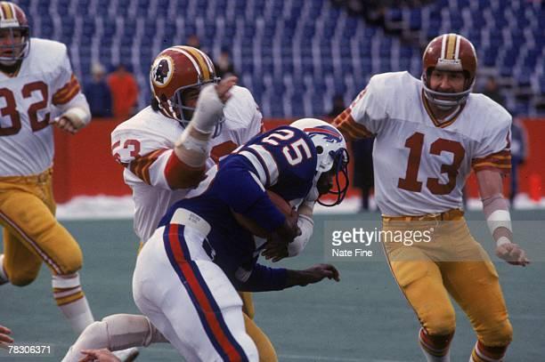 Linebacker Harold McClinton and safety Jake Scott of the Washington Redskins stops running back Roland Hooks of the Buffalo Bills on December 4 1977...