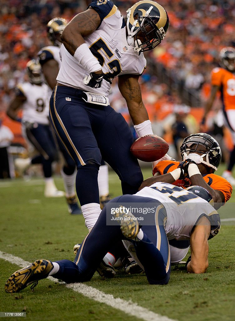 Linebacker Jabara Williams #52 of the St. Louis Rams strips the ball away from running back Ronnie Hillman #21 of the Denver Broncos as cornerback Cortland Finnegan #31 applies a hit during the first quarter at Sports Authority Field Field at Mile High on August 24, 2013 in Denver, Colorado.