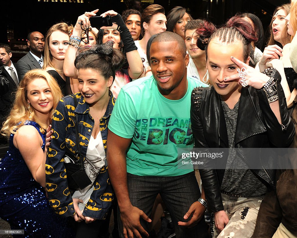 Linebacker James Anderson (C) and designer Indashio pose with models and fans at the Indashio fall 2013 fashion show during Mercedes-Benz Fashion Week at Grand Central Station on February 13, 2013 in New York City.