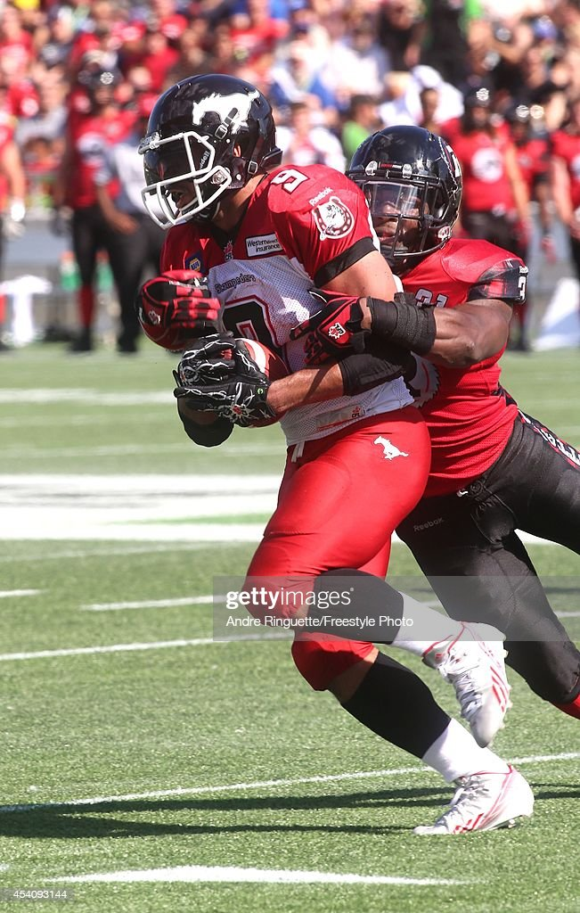 Linebacker Jasper Simmons #31 of the Ottawa Redblacks wraps up Jon Cornish #9 of the Calgary Stampeders as he rushes with the ball during a CFL game at TD Place Stadium on August 24, 2014 in Ottawa, Ontario, Canada.