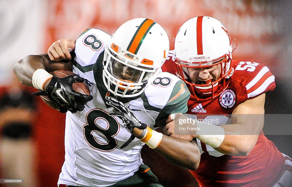 Linebacker Josh Banderas #52 of the Nebraska Cornhuskers wraps up running back <a gi-track='captionPersonalityLinkClicked' href=/galleries/search?phrase=Duke+Johnson+-+Jogador+de+futebol+americano&family=editorial&specificpeople=13981151 ng-click='$event.stopPropagation()'>Duke Johnson</a> #8 of the Miami Hurricanes during their game at Memorial Stadium on September 20, 2014 in Lincoln, Nebraska. Nebraska defeated Miami 41-31.