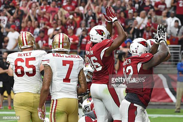 Linebacker Kareem Martin and defensive end Frostee Rucker of the Arizona Cardinals signal safety in the third quarter of the NFL game against the San...