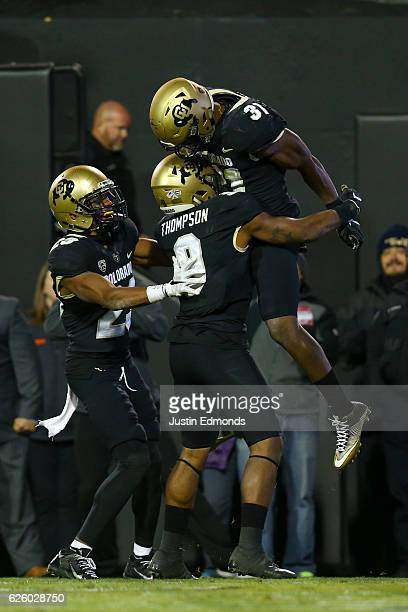 Linebacker Kenneth Olugbode of the Colorado Buffaloes celebrates his fumble recovery and return for a touchdown with defensive back Tedric Thompson...