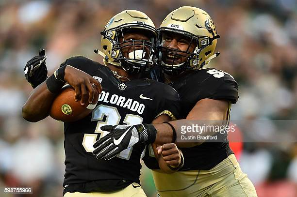 Linebacker Kenneth Olugbode of the Colorado Buffaloes celebrates with defensive tackle Samson Kafovalu after recovering a fumble after a sack against...