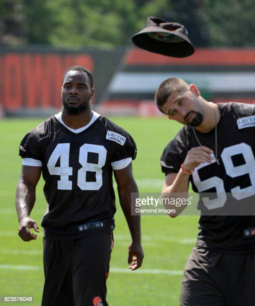 Linebacker Ladell Fleming of the Cleveland Browns walks off the field as linebacker Tank Carder attempts to catch his hat on his head following a...