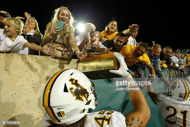 Linebacker Lucas Wacha of the Wyoming Cowboys hoists The Bronze Boot to fans after defeating Colorado State Rams 3817 in the border war at Sonny...