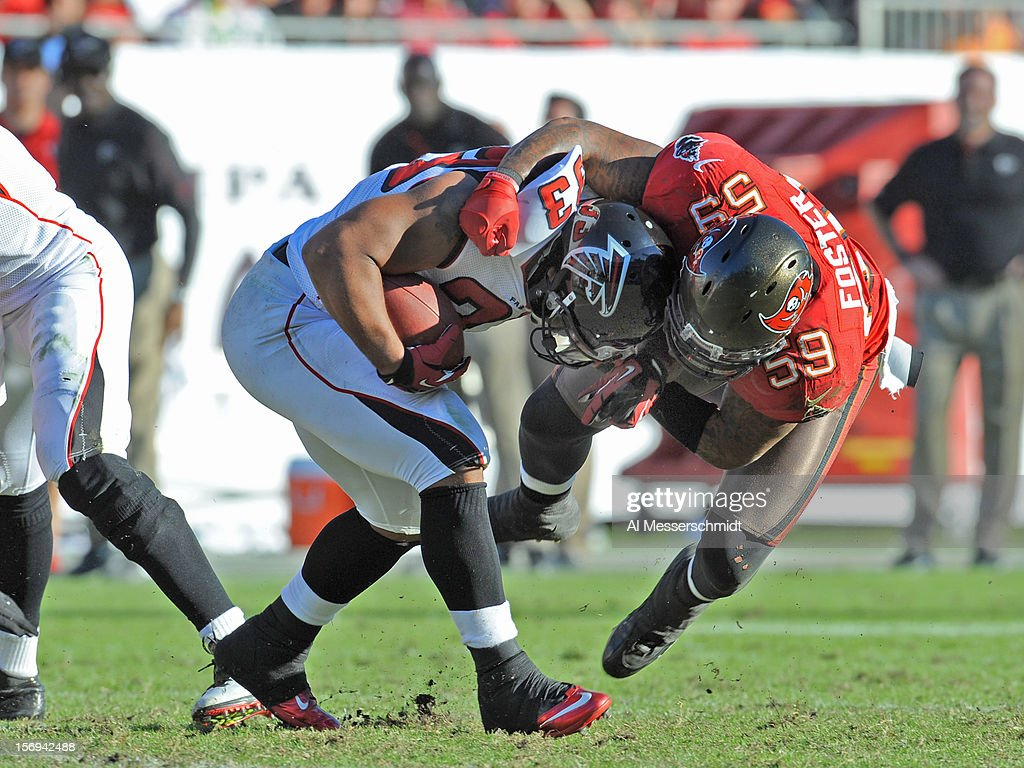 Linebacker <a gi-track='captionPersonalityLinkClicked' href=/galleries/search?phrase=Mason+Foster&family=editorial&specificpeople=5509834 ng-click='$event.stopPropagation()'>Mason Foster</a> #59 of the Tampa Bay Buccaneers tackles running back Michael Turner #33 of the Atlanta Falcons November 25, 2012 at Raymond James Stadium in Tampa, Florida.