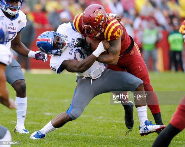 Linebacker Osaze Ogbebor of the Kansas Jayhawks tackles running back David Montgomery of the Iowa State Cyclones as he rushed for yards in the second...