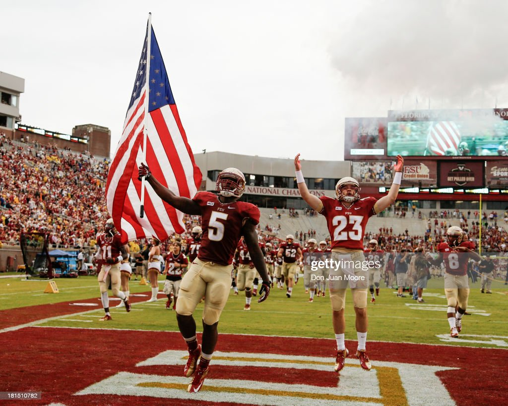 Linebacker Reggie Northrup #5 of the Florida State Seminoles carries the United States flag before the game against the Bethune-Cookman Wildcats on Military Appreciation Day at Doak Campbell Stadium on Bobby Bowden Field on September 21, 2013 in Tallahassee, Florida. The 8th ranked Florida State Seminoles defeated the Bethune-Cookman Wildcats 54-6.