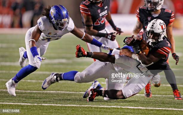 Linebacker Rico Tolefree and defensive tackle Ricky LeungWai of the San Jose State Spartans tackle running back Devonta'e HenryCole of the Utah Utes...