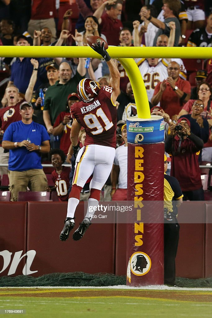 Linebacker Ryan Kerrigan of the Washington Redskins dunks the ball over the goalpost after intercepting a pass and returning it for a touchdown...
