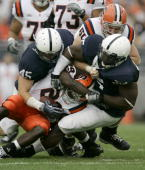Linebacker Sean Lee and tackle Ollie Ogbu of the Penn State Nittany Lions tackle running back Antwon Bailey of the Syracuse Orangemen during the...