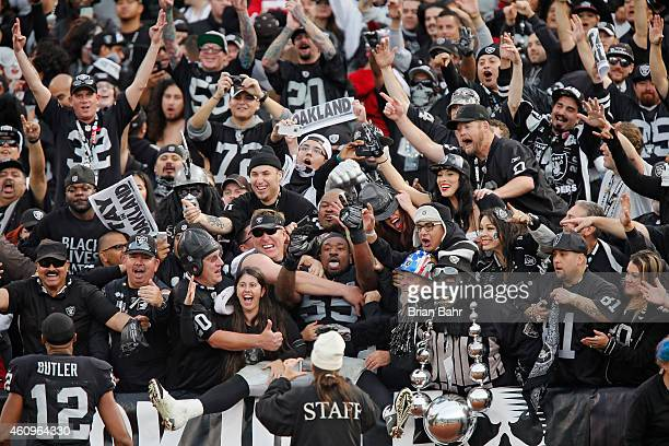 Linebacker Sio Moore of the Oakland Raiders jumps into arms of fans in the Black Hole after defeating the San Francisco 49ers on December 7 2014 at...