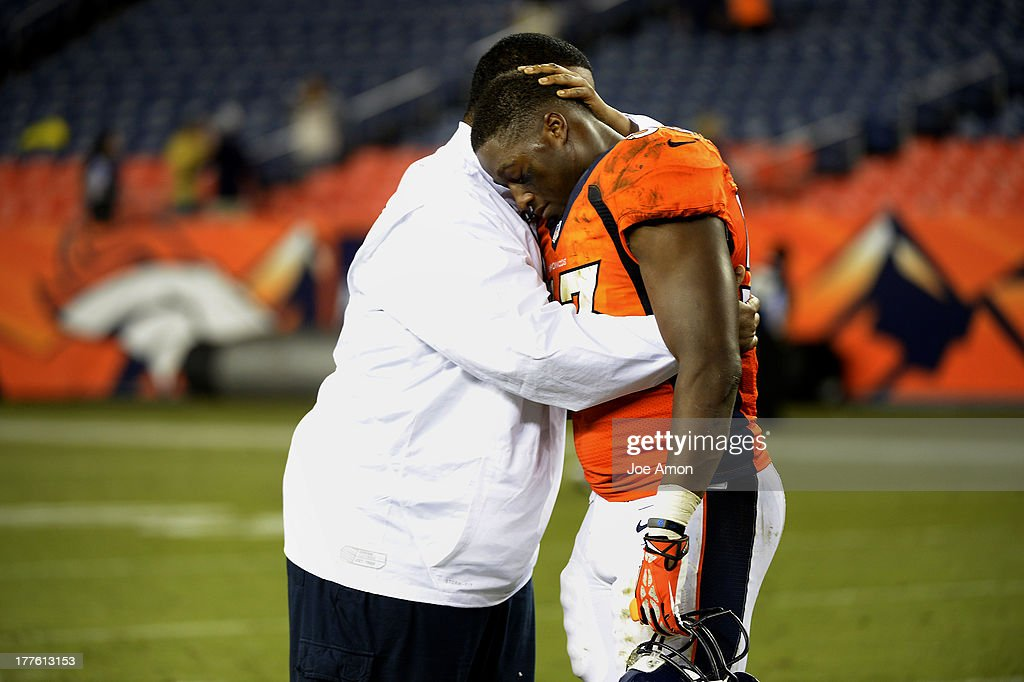 Linebacker Steven Johnson (53) of the Denver Broncos is hugged after the game by the team Chaplin Chip Simmons after the teams win vs the St. Louis Rams during the 3rd pre-season game of the season at Sports Authority Field at Mile High. August 24, 2013 Denver, Colorado.