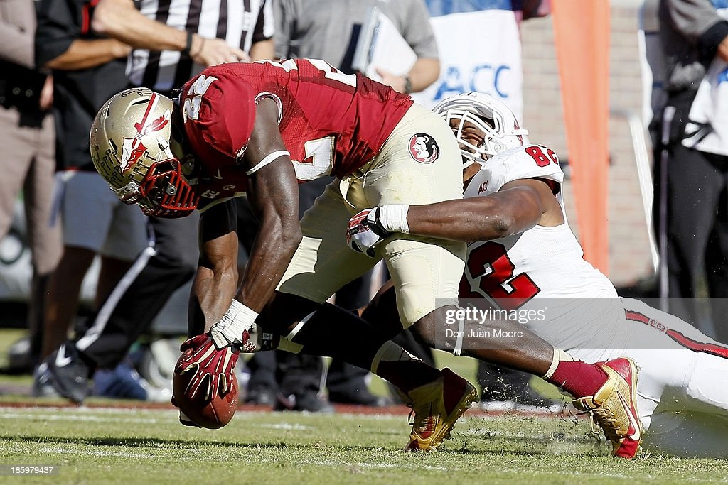 Linebacker Telvin Smith #22 of the Florida State Seminoles is tackled by tight end Asa Watson #82 North Carolina State Wolfpack after a fumble during the game at Bobby Bowden Field at Doak Campbell Stadium on October 26, 2013 in Tallahassee, Florida. The 3rd ranked Florida State Seminoles defeated North Carolina State Wolfpack 49-17.
