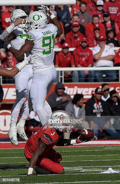 Linebacker Troy Dye and defensive lineman TJ Daniel of the Oregon Ducks celebrate a first half sack of quarterback Troy Williams of the Utah Utes at...