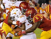 Linebacker Willie Harvey and linebacker Jordan Harris of the Iowa State Cyclones wrap up running back Johnathan Gray of the Texas Longhorns as he...