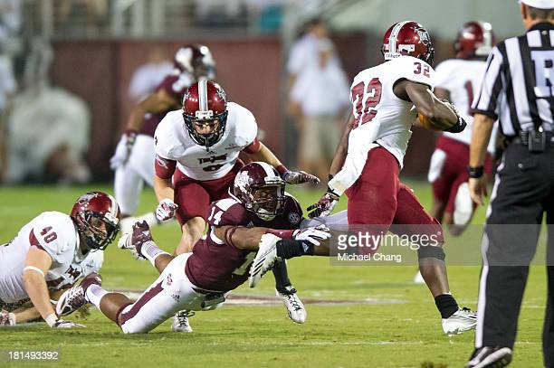 Linebacker Zach Jackson of the Mississippi State Bulldogs attempts to tackle running back Brandon Burks of the Troy Trojans during the first half of...