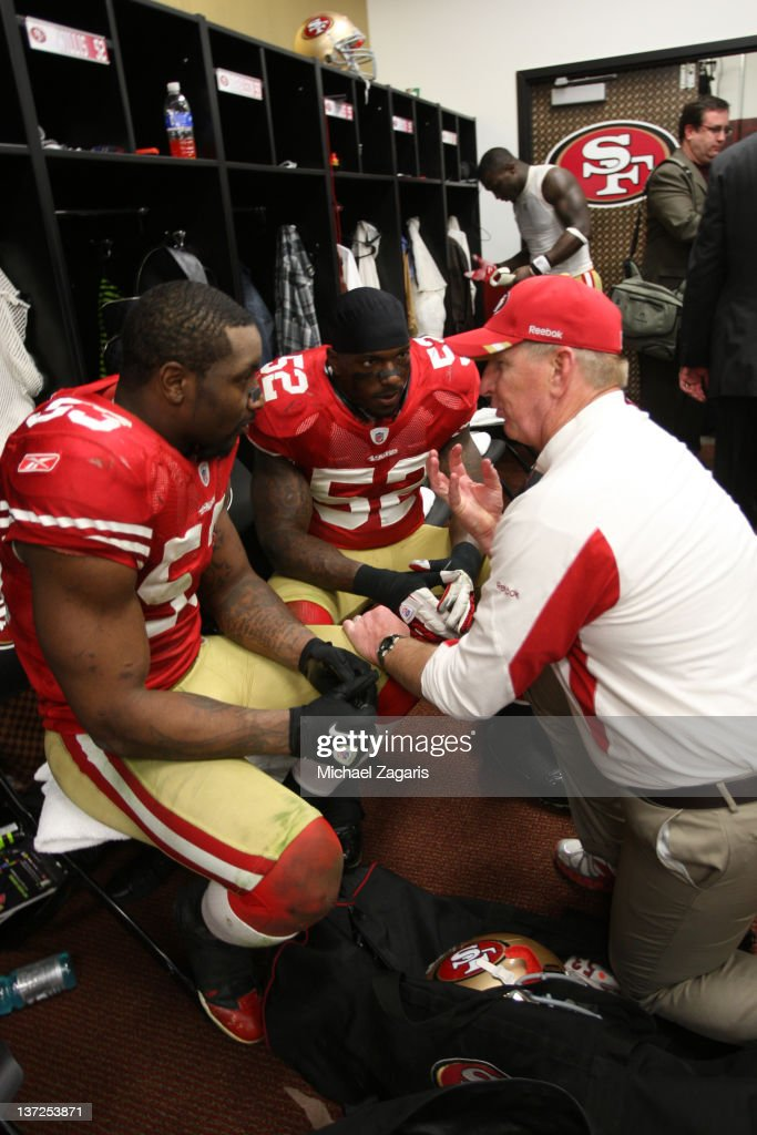 Linebackers Coach Jim Leavitt of the San Francisco 49ers talks with Patrick Willis and NaVorro Bowman in the locker room following the game against...