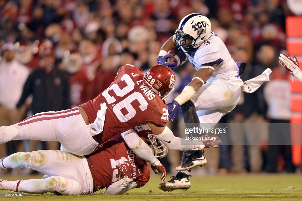 Linebackers Jordan Evans #26 and Eric Striker #19 of the Oklahoma Sooners try to tackle running back Shaun Nixon #3 of the TCU Horned Frogs on November 21, 2015 at the Gaylord Family Oklahoma Memorial Stadium in Norman, Oklahoma.