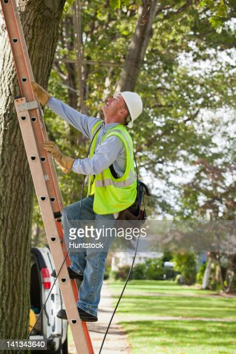 Lineman climbing a ladder to work on wires : Foto de stock