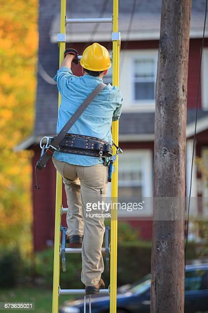 Lineman climbing ladder at power pole