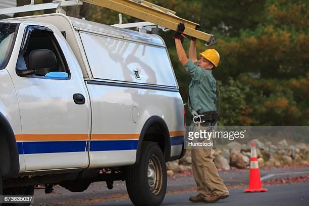Lineman putting ladder back on truck at site