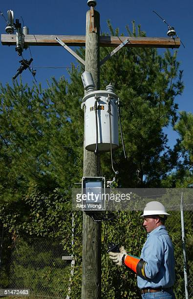 Lineman Randy Harless demostrates the installation of a coupler for injecting signals onto power lines during a tour to view the Broadband Over Power...
