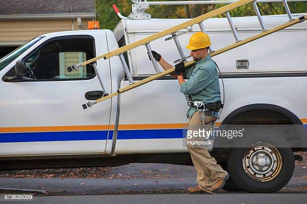 Lineman taking ladder from truck at site