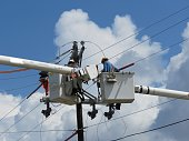 linemen in utility truck working on electrical equipment