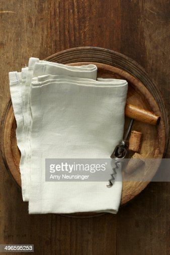 Linen napkins with corkscrew in wooden bowls.