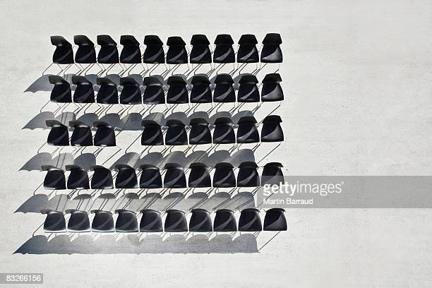 Lines of empty office chairs with one missing