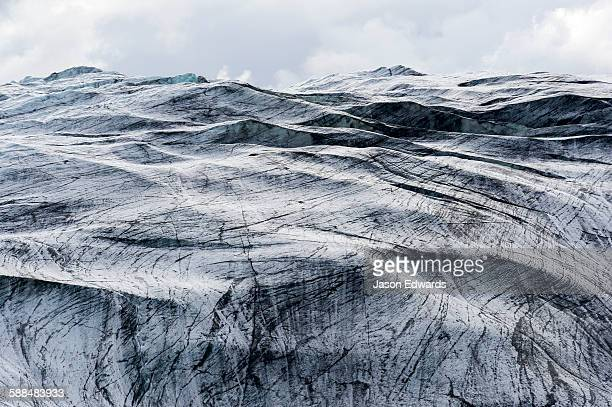 Lines scar the ice on the inhospitable surface of a glacier.