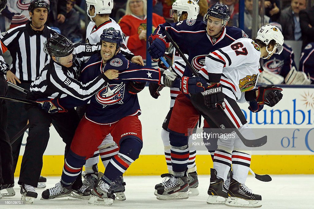 Linesman Andy McElman #90 holds back Derek Mackenzie #24 of the Columbus Blue Jackets from trying to fight <a gi-track='captionPersonalityLinkClicked' href=/galleries/search?phrase=Michael+Frolik&family=editorial&specificpeople=537965 ng-click='$event.stopPropagation()'>Michael Frolik</a> #67 of the Chicago Blackhawks during the third period on January 26, 2013 at Nationwide Arena in Columbus, Ohio. Chicago defeated Columbus 3-2.