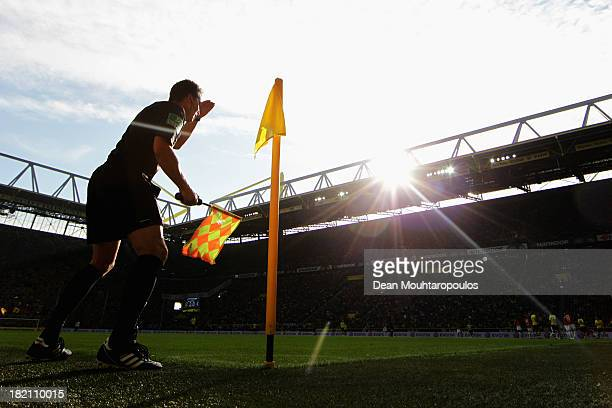 Linesman / Assistant referee Wolfgang Walz covers his eyes from th sun glare during the Bundesliga match between Borussia Dortmund and SC Freiburg at...